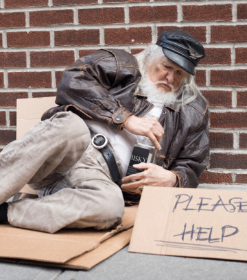 Homeless man sitting on a street with sign